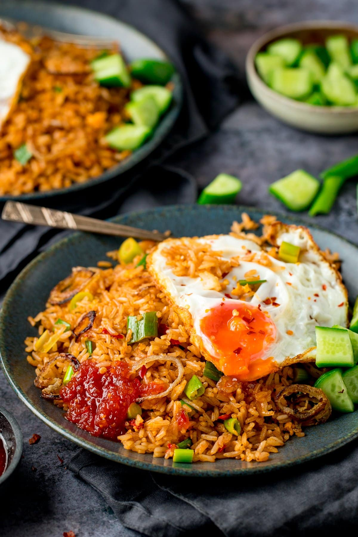 nasi goreng rice on a plate, with a fried egg, chilli sauce and cucumber