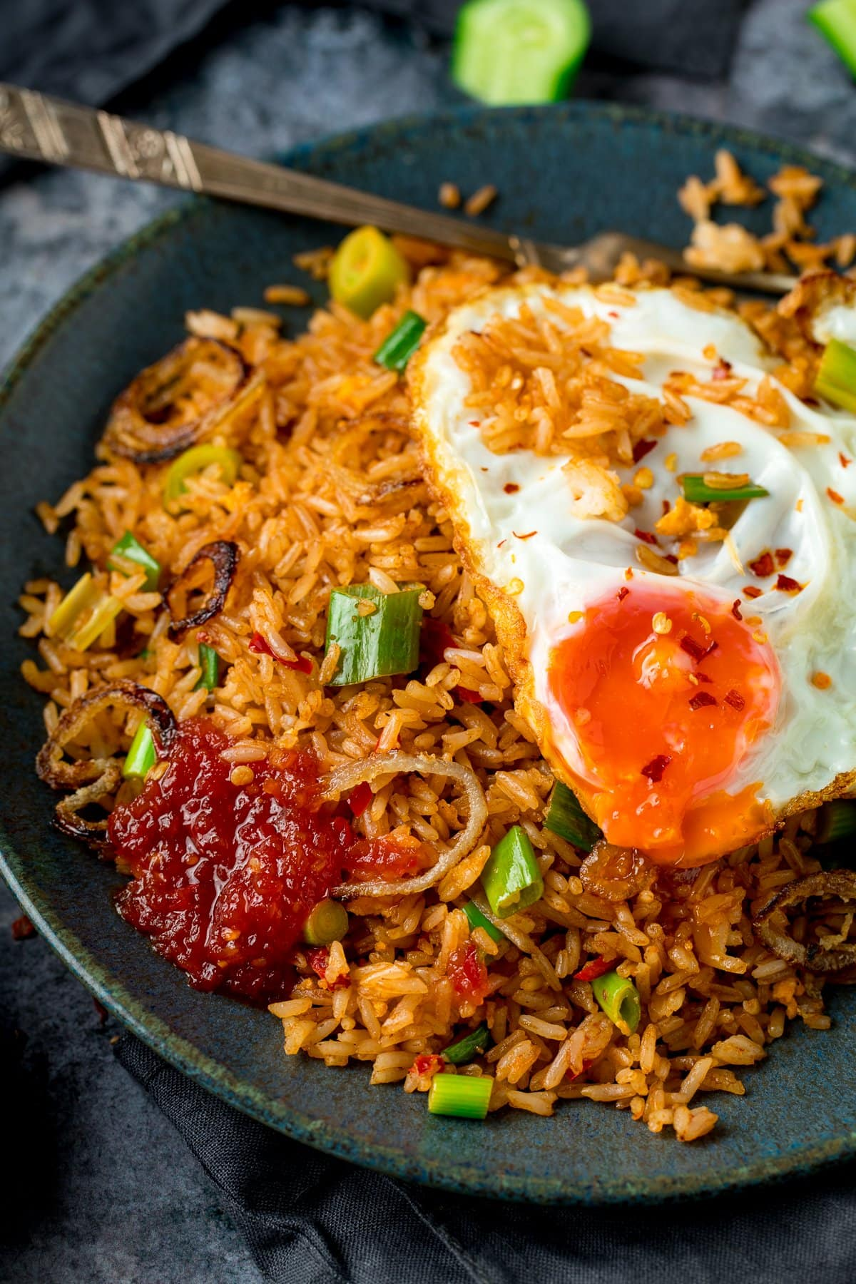 nasi goreng rice on a plate, topped with a fried egg and chilli sauce