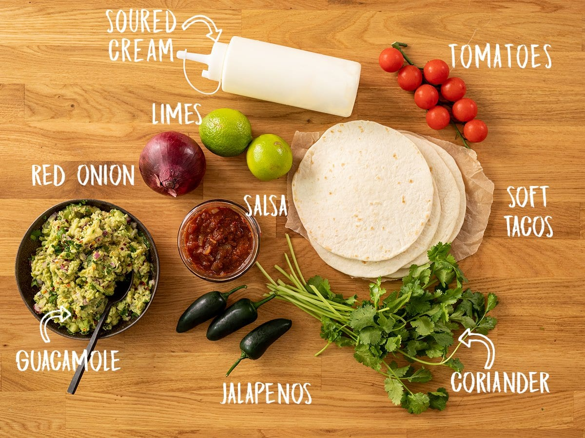 Tacos and toppings for lamb carnitas tacos on a wooden board