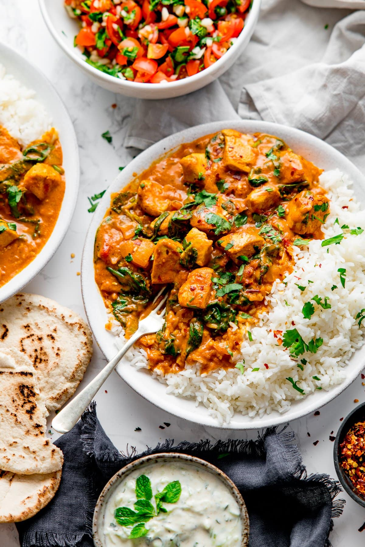 White bowl with chicken curry and rice with a fork digging into the curry. Ingredients and side dishes scattered around.