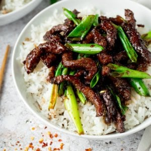 Mongolian Beef and spring onions on top of rice in a white bowl