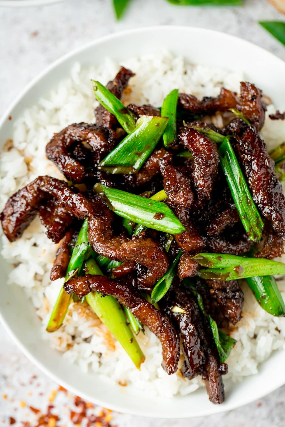 Close up overhead shot of Mongolian Beef and rice in a white bowl