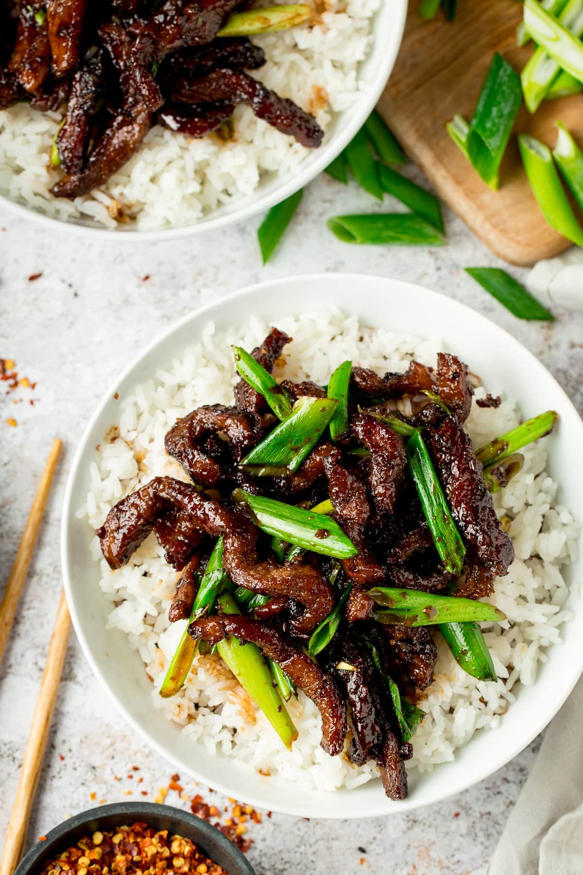 Mongolian Beef and rice in a white bowl on a light background with chopsticks and ingredients scattered around
