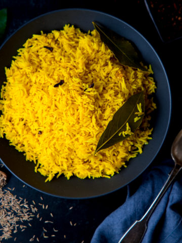 Square image of Pilau rice in a black bowl on a dark surface