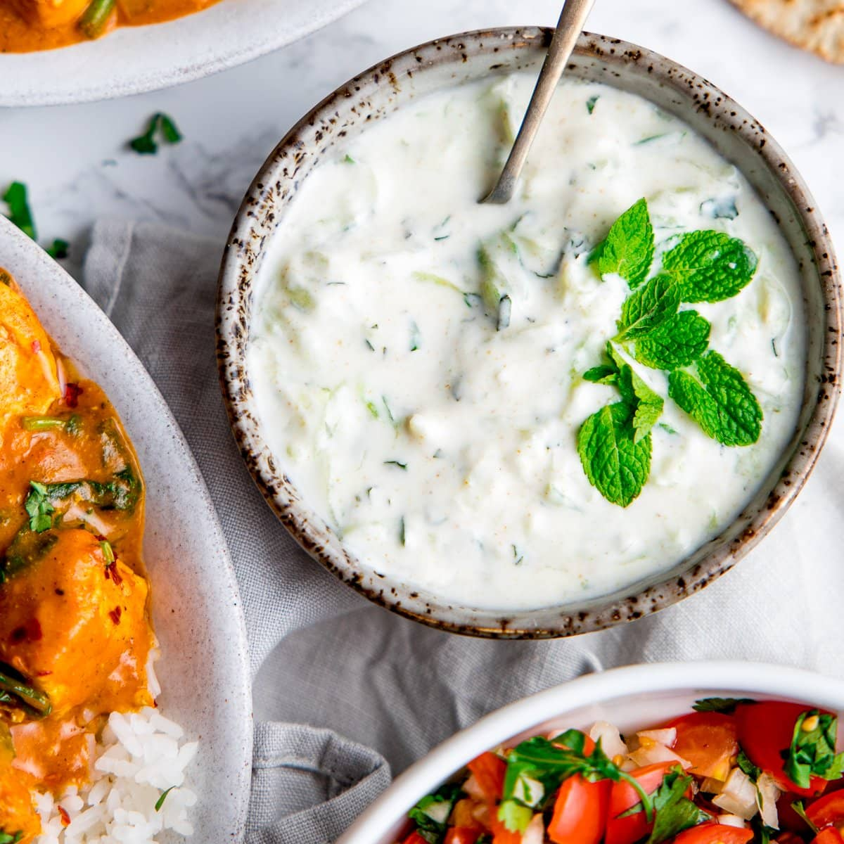 Raita in a grey bowl with mint leaves on top and bowls of food around the raita