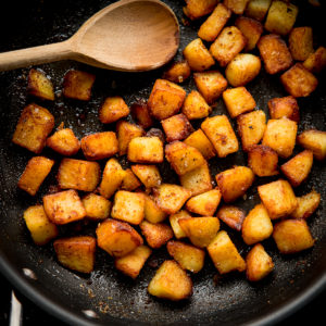 Square image of saute potatoes in a pan with a wooden spoon