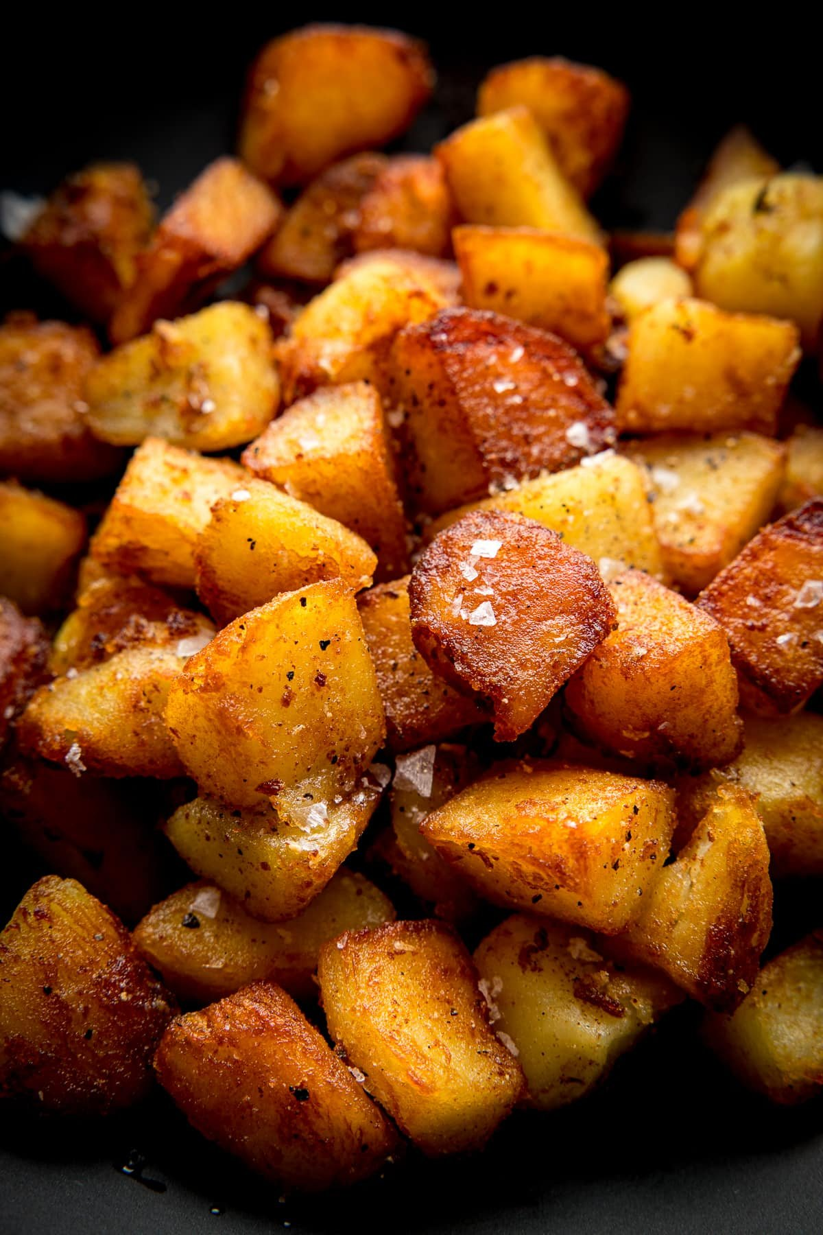 Close up image of a pile of crispy saute potatoes in a dark bowl topped with a sprinkling of salt