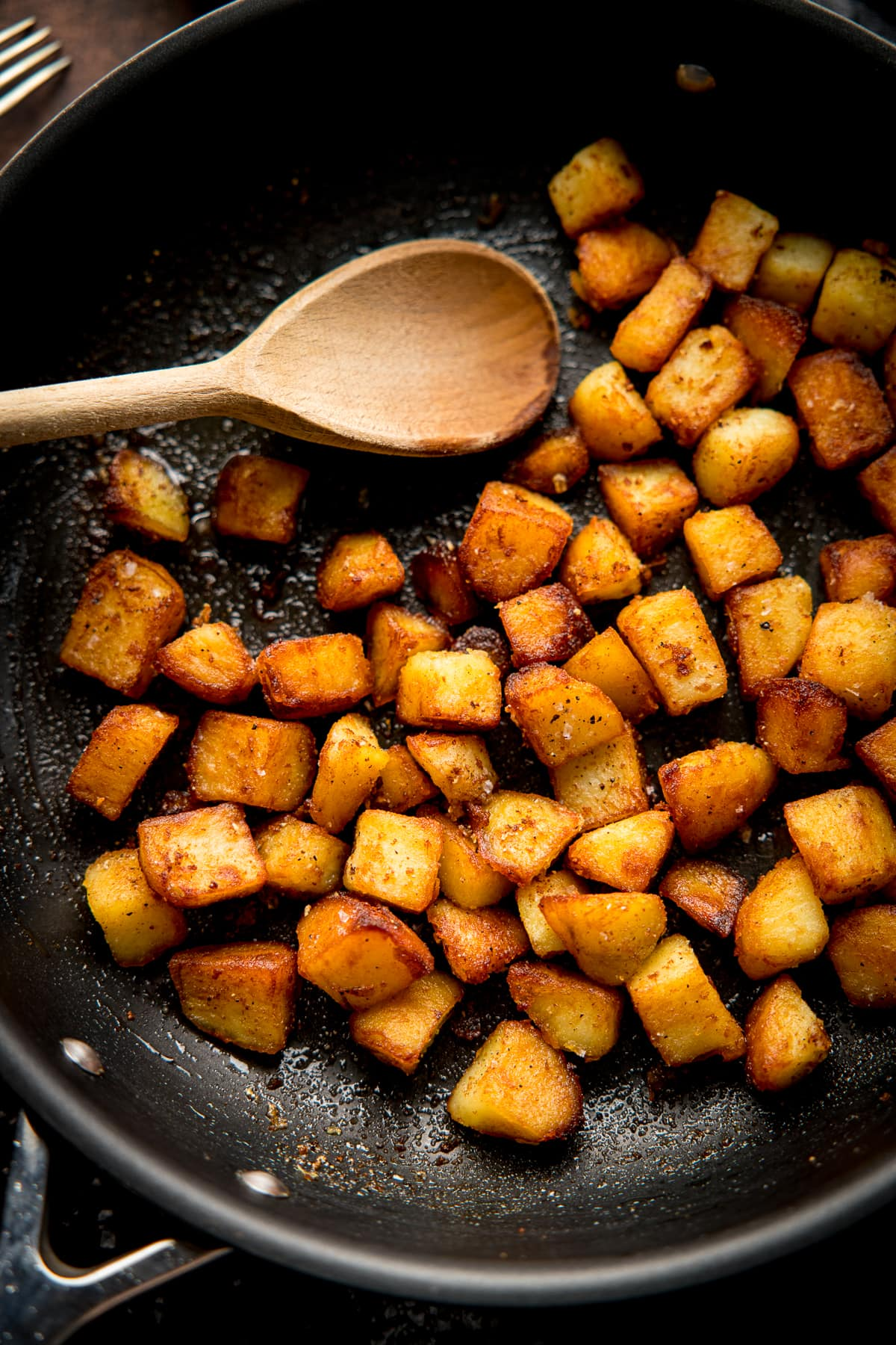 saute potatoes in a dark pan with a wooden spoon