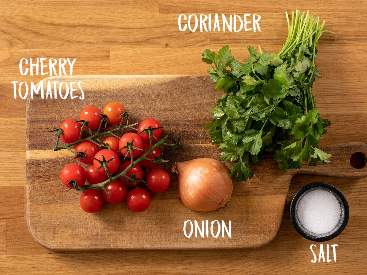 Ingredients for tomato, onion and coriander salad on a wooden table