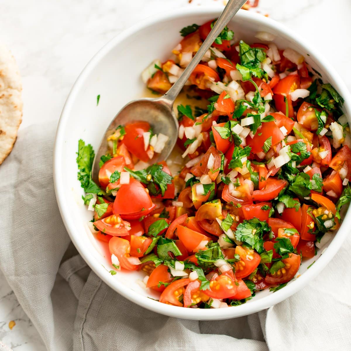 tomato, onion and coriander chopped salad in a white bowl on a light background. Spoon in the salad.