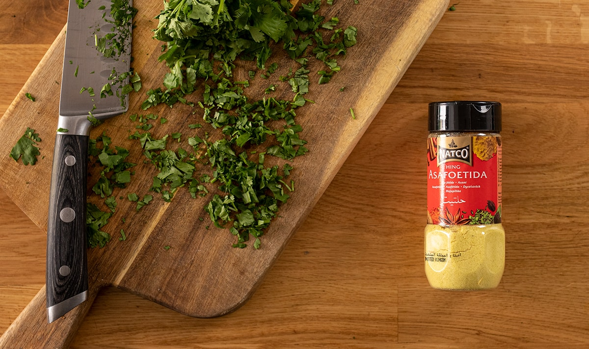 Jar of asafoetida powder on a wooden table next to chopped coriander.