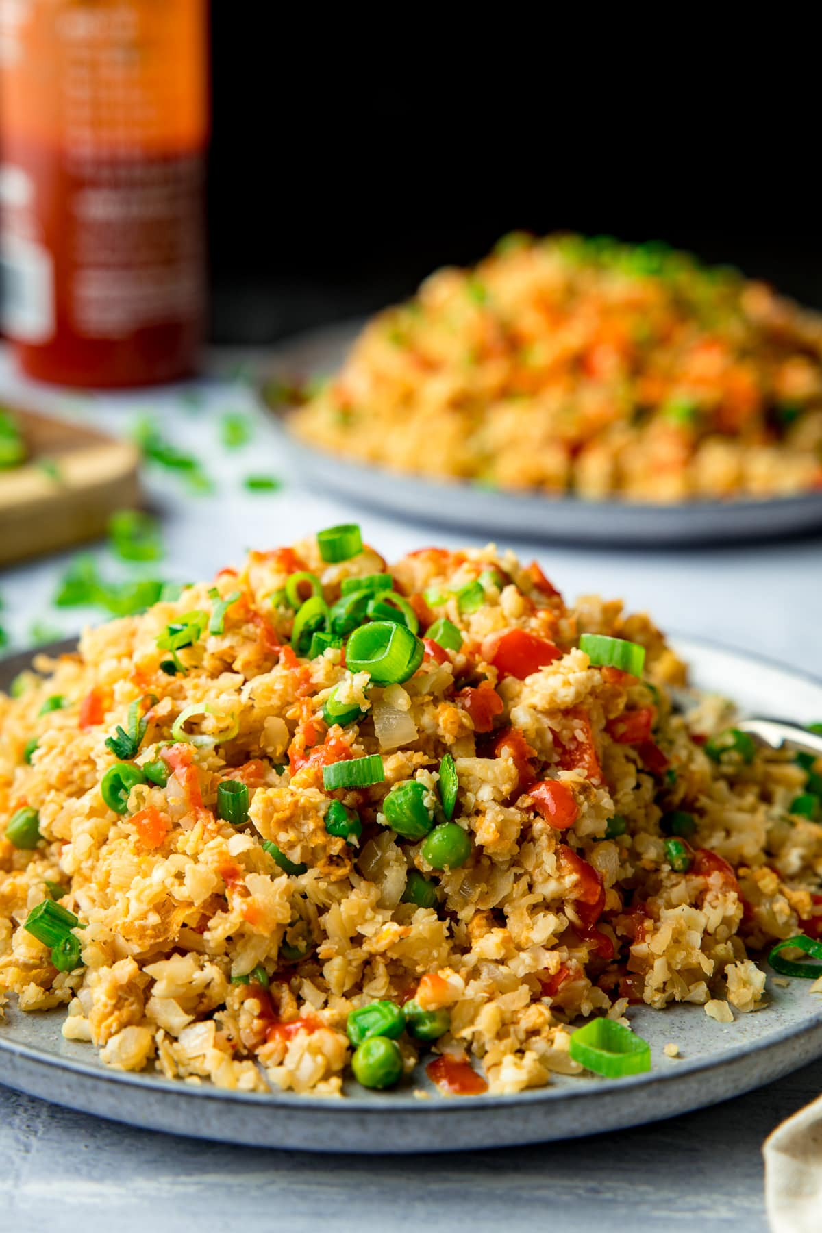 Cauliflower fried rice piled up on a plate with a further plate and chilli sauce bottle in the background