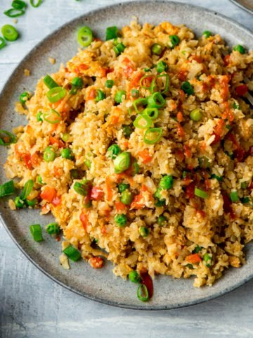 Cauliflower fried rice on a grey plate on a light background