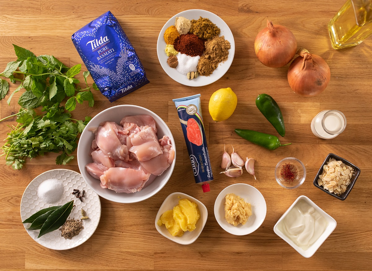 Ingredients for chicken biryani on a wooden table