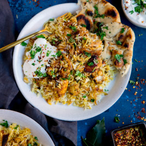 chicken biryani topped with natural yogurt on a white plate on a blue background.