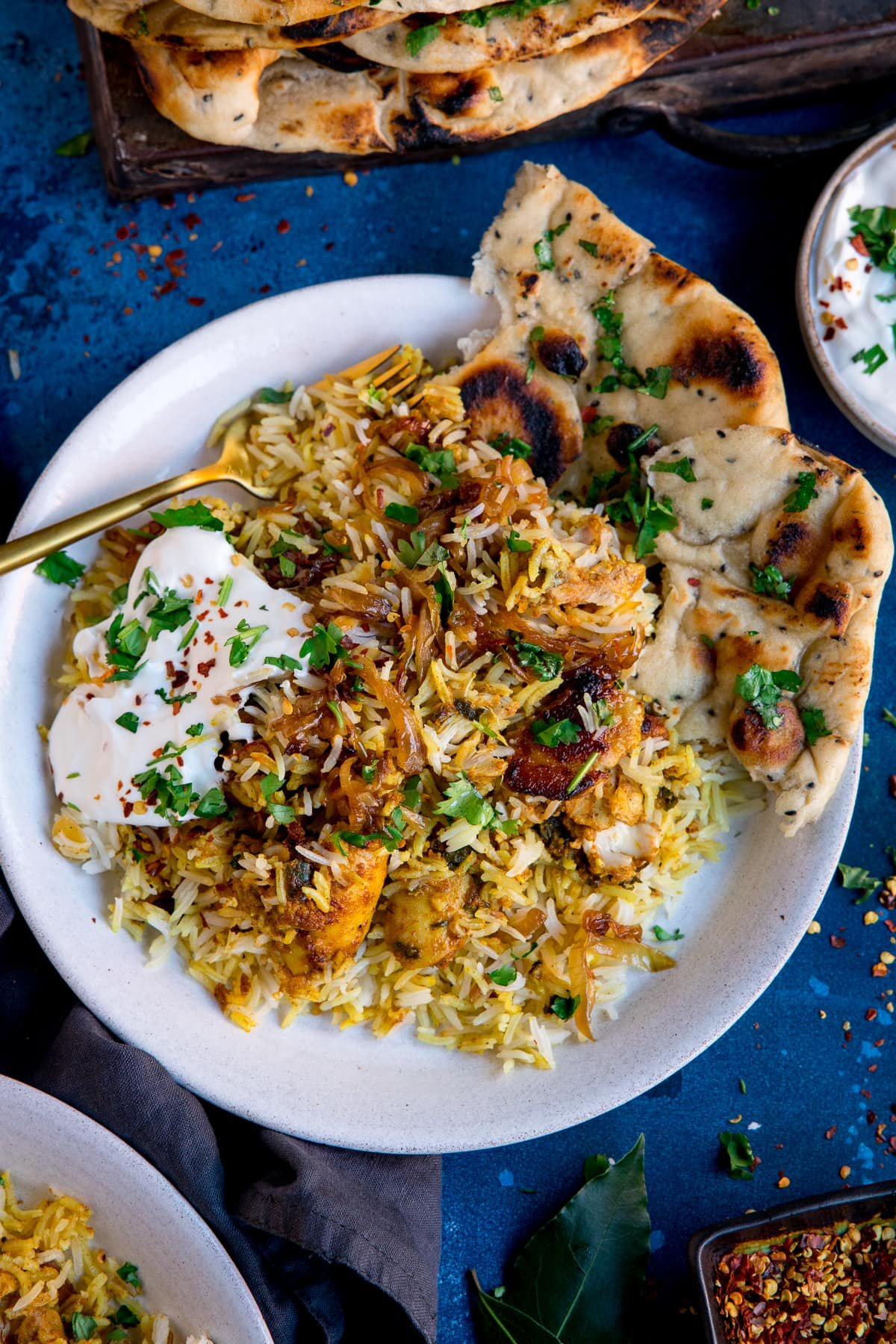 chicken biryani and natural yogurt on a plate with naan bread. Plate is on a blue background.