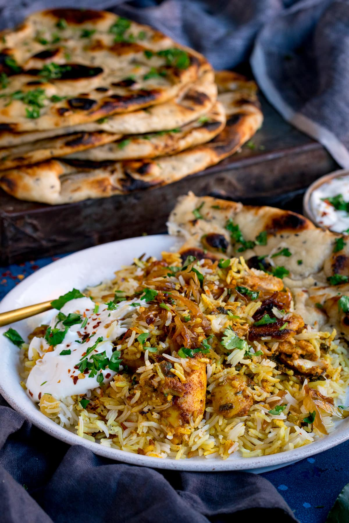 Plate of chicken biryani with pile of naan breads in the background