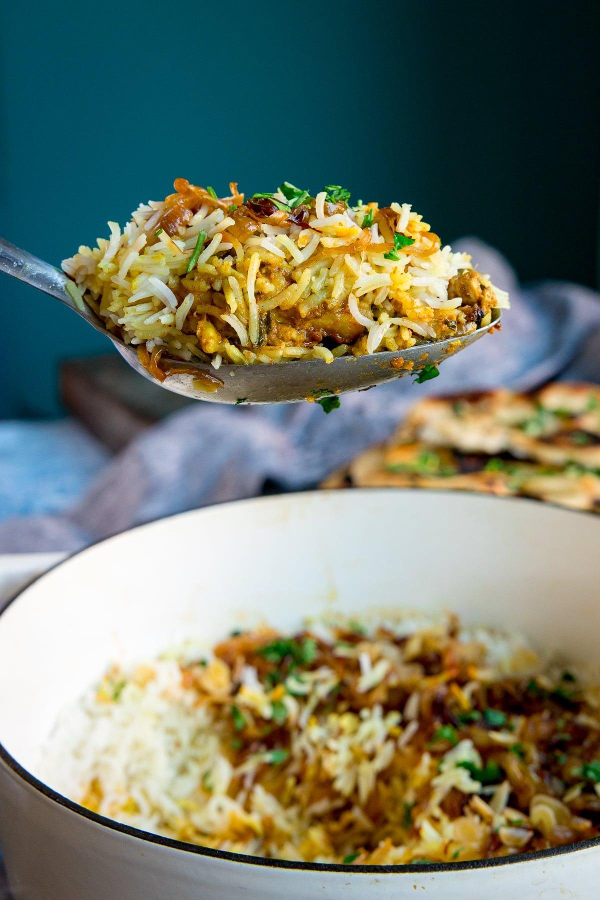 Serving spoonful being take form a pan of chicken biryani.