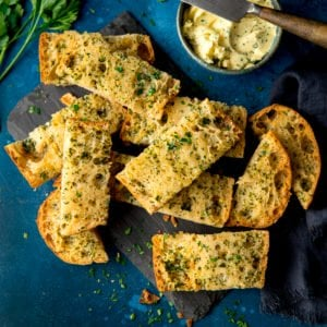 Sliced of garlic bread on a dark blue background with a bowl of garlic butter and knife at the top of the frame