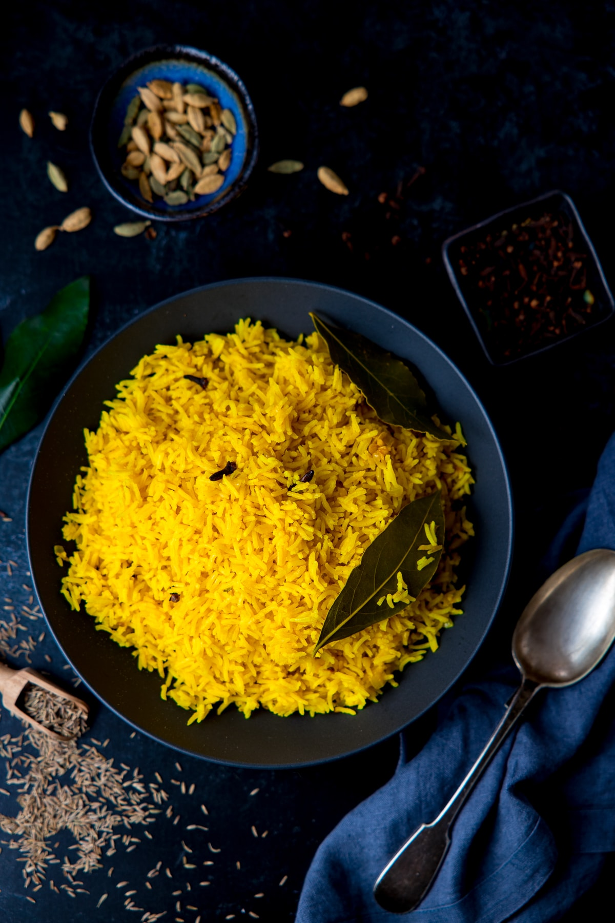 Pilau rice in a black bowl on a dark surface with ingredients scattered around