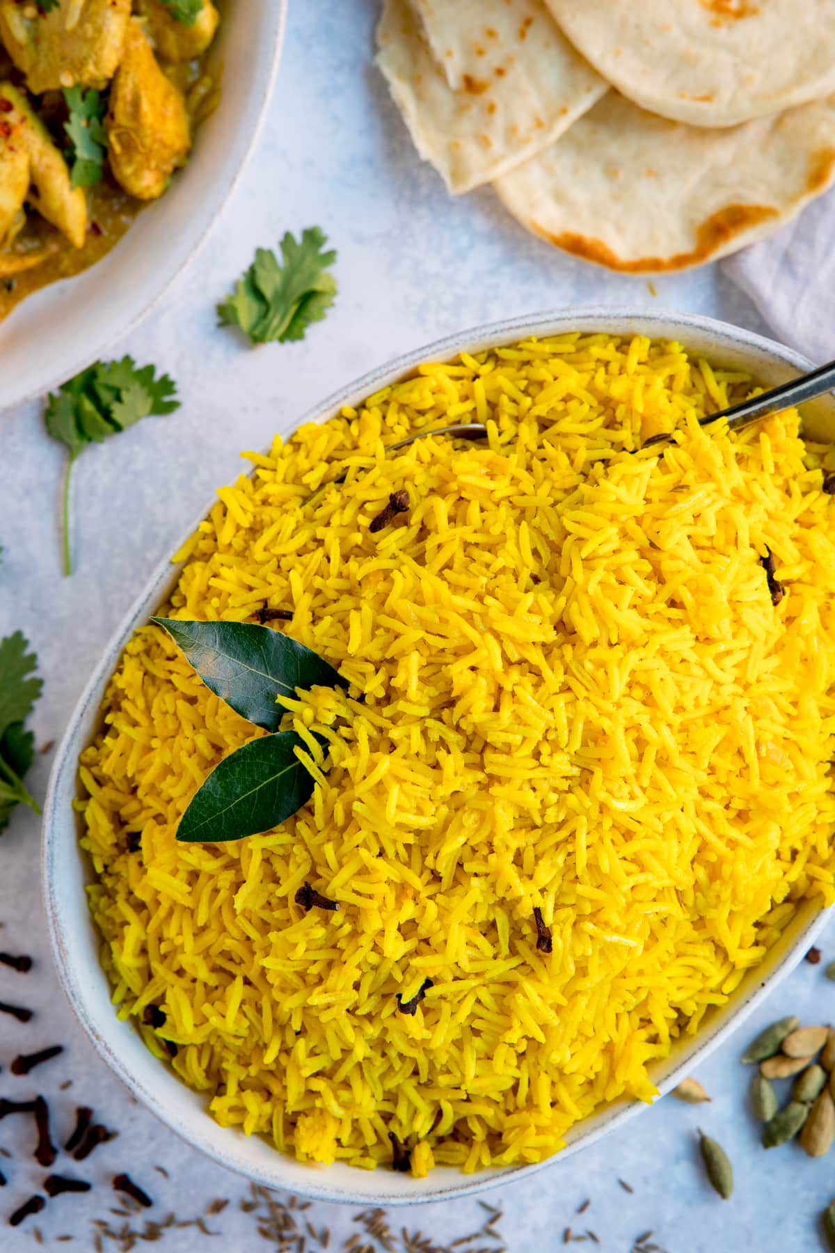 Pilau rice in a white bowl on a light background. Flatbreads and plate of curry just in frame