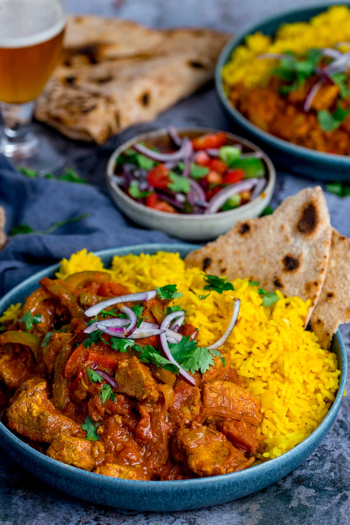 Pilau rice with chicken jalfrezi in a blue bowl on a blue background. Further dishes scattered around.