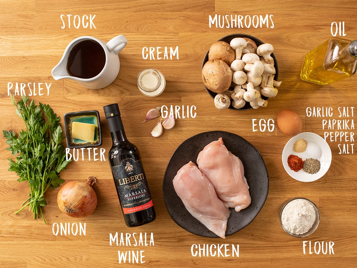 Ingredients for chicken marsala on a wooden table