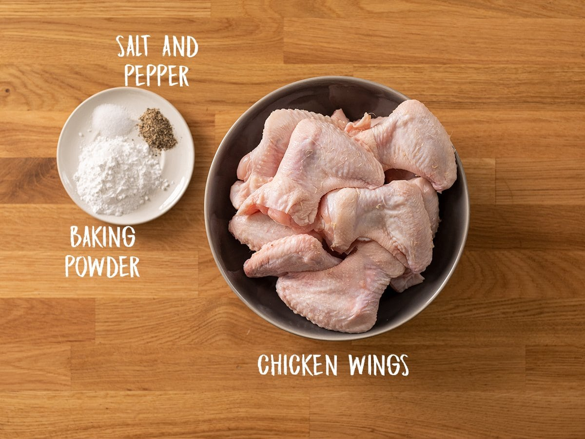 Ingredients for crispy chicken wings on a wooden table