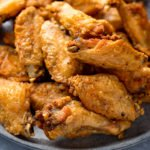 Close up image of crispy chicken wings piled up on a grey plate.