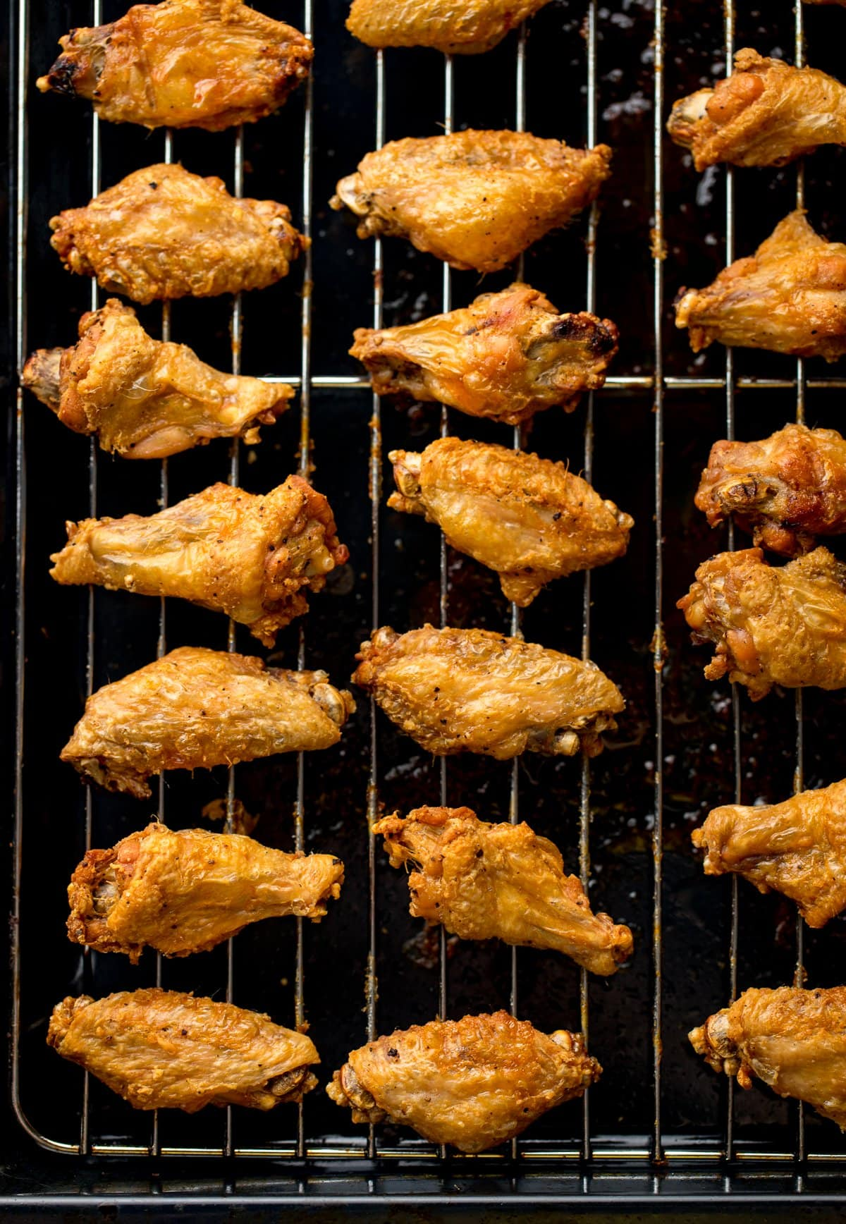 Overhead shot of crispy chicken wings lined up on a wire rack over a dark tray.