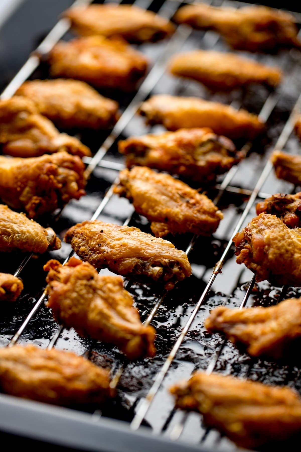 Cooked crispy chicken wings on a wire rack over a dark tray.