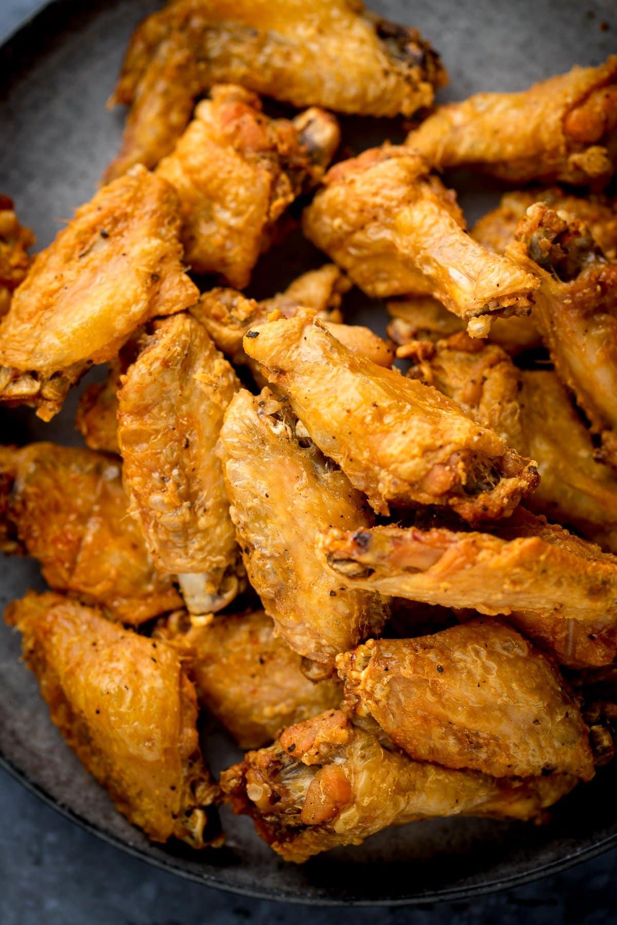 Pile of crispy chicken wings on a dark plate.