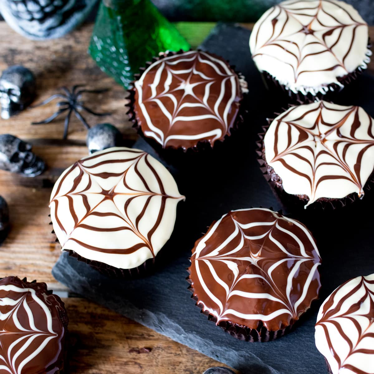 Chocolate Halloween cupcakes with spiderweb patterns in the topping placed on a dark slate background with toy skulls and spiders in the background.