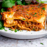 Portion of lasagne on a white plate with salad in the background