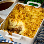 shepherds pie in a white baking dish on a blue and white cloth