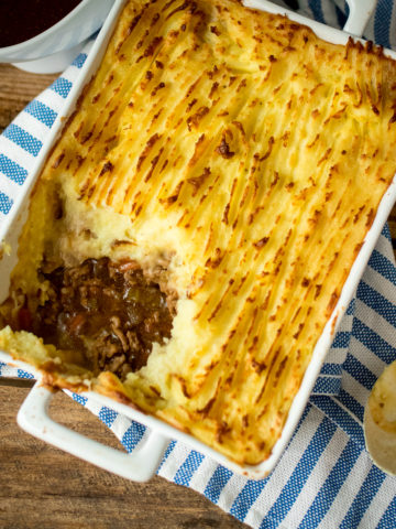 Shepherd's pie in a white baking dish and a scoop full has been take out
