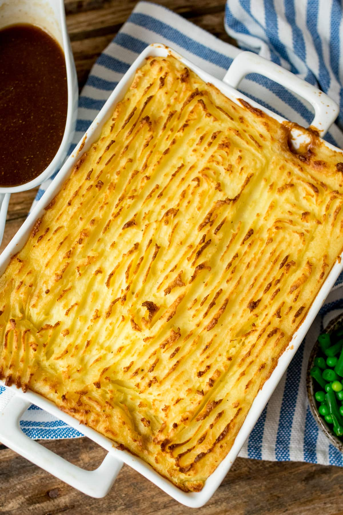 Overhead of white baking dish with shepherds pie with crispy topping with a jug of gravy in the top left corner.