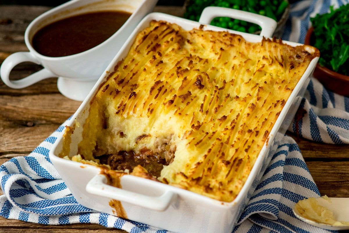 Dish of Shepherd's pie with scoop taken out on a blue and white strip kitchen towel.