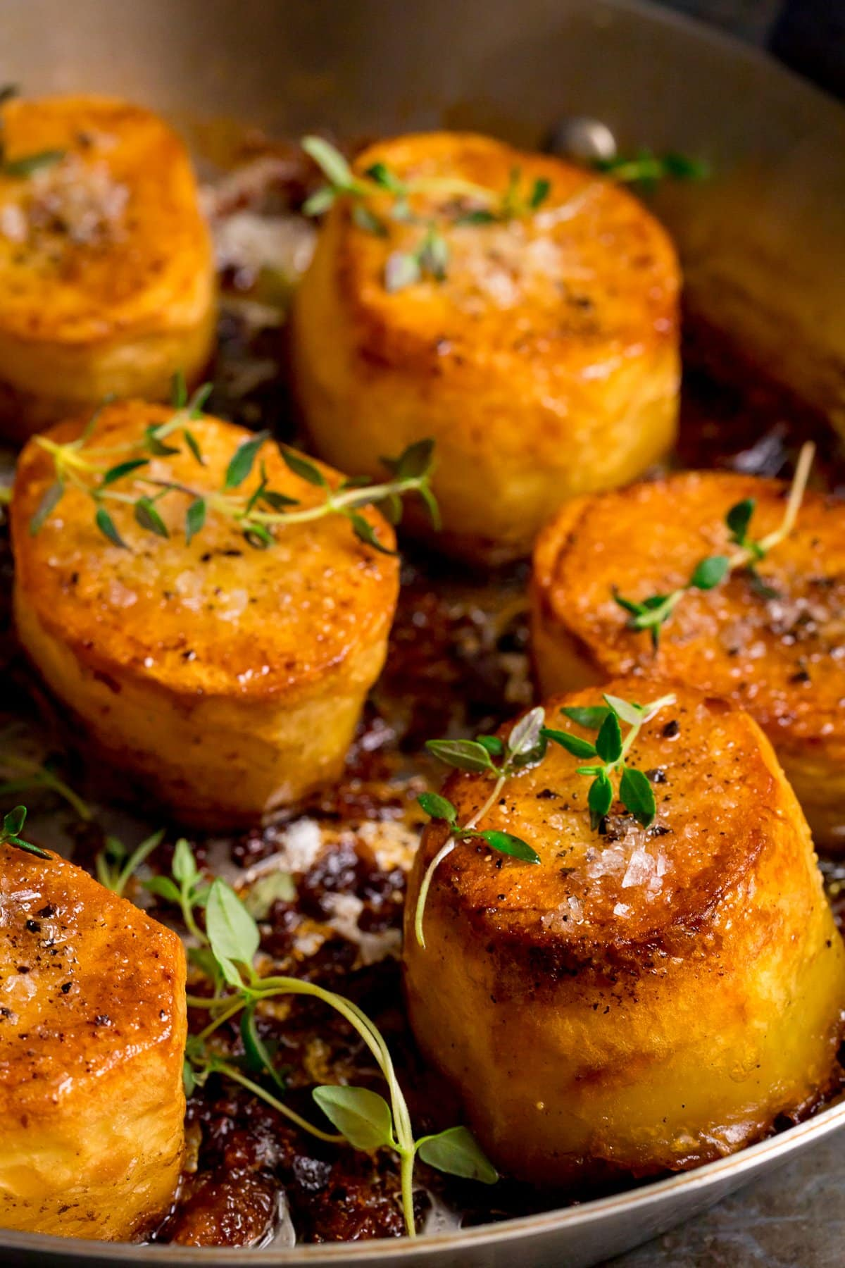 Close up of fondant potatoes in a frying pan, topped with fresh thyme