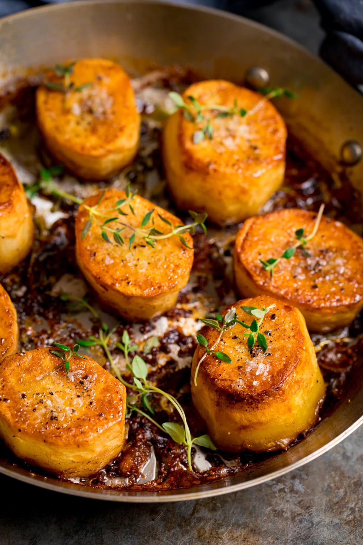 fondant potatoes in a pan topped with thyme and salt