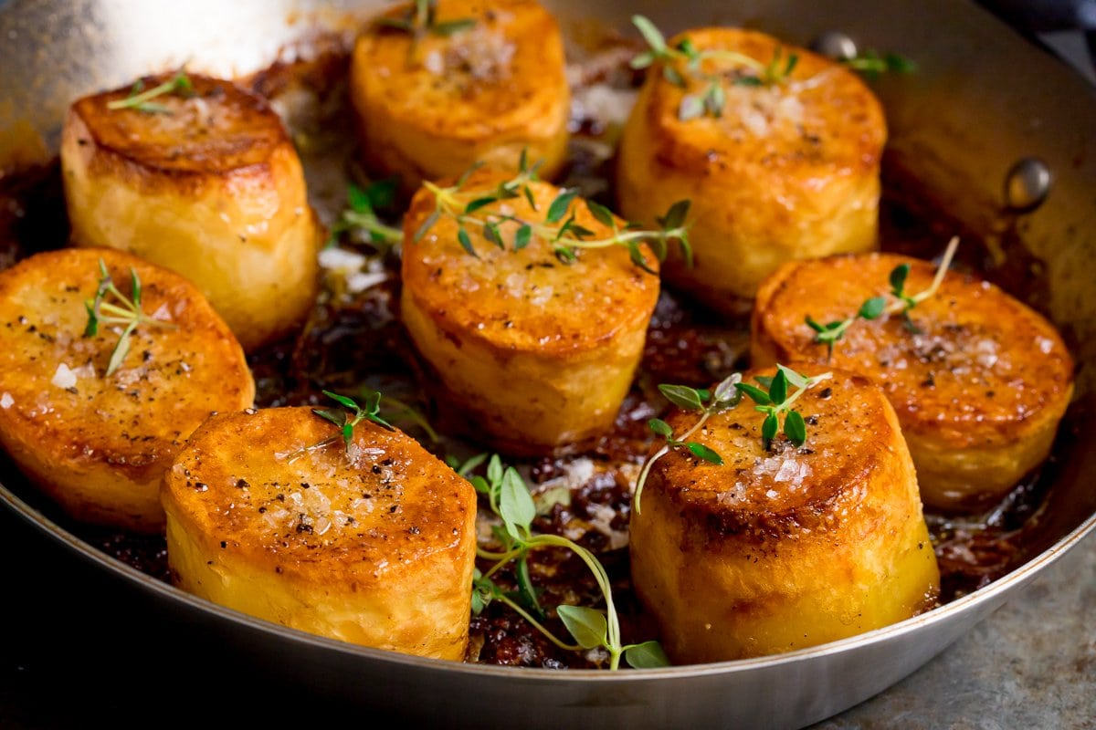 Wide image of fondant potatoes in a pan topped with fresh thyme