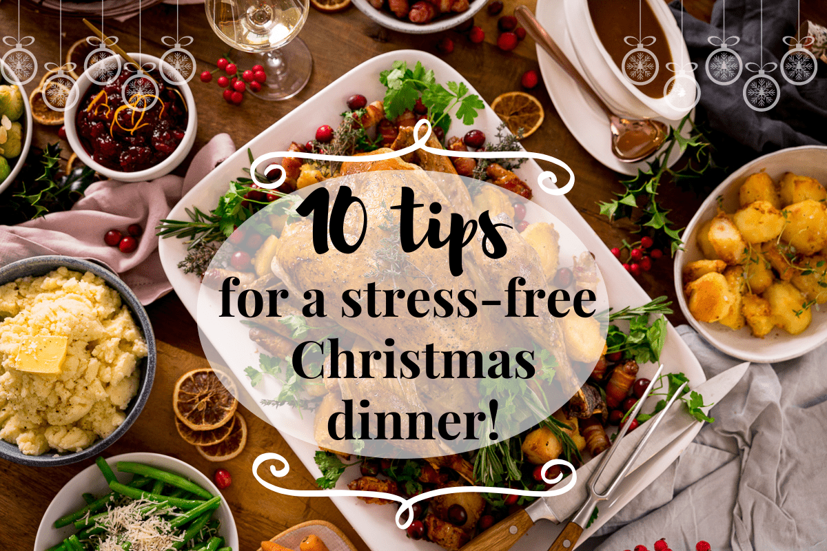 Wide Infographic showing text for 10 tips for a stress-free Christmas dinner on the background of a Christmas dinner table filled with food.