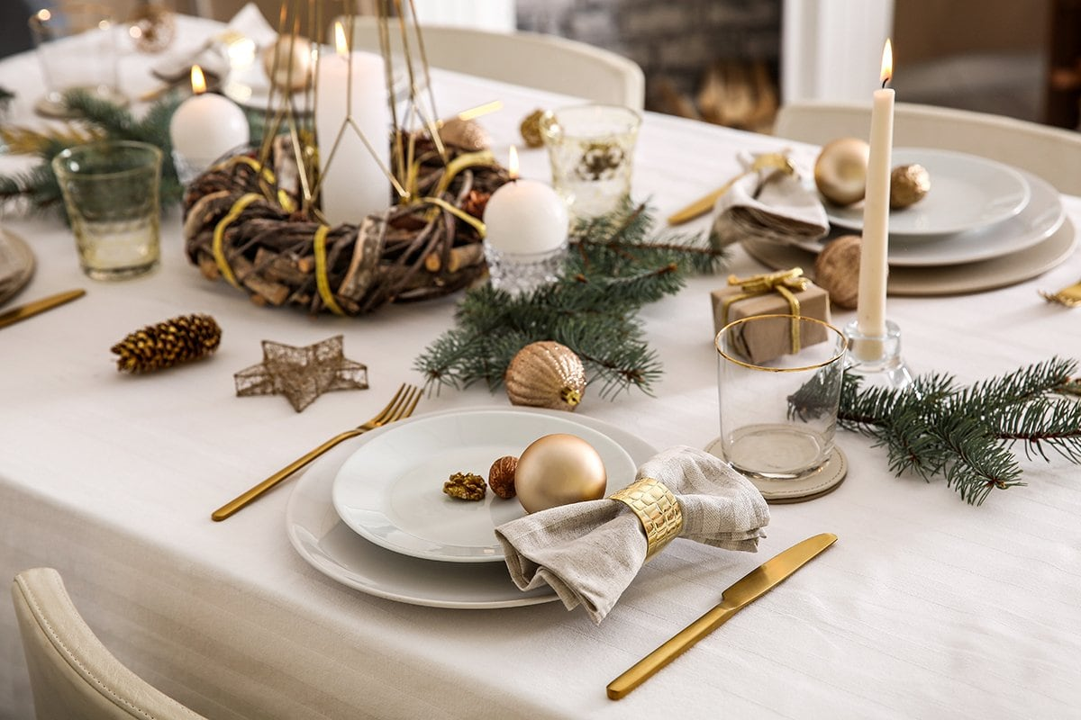 Table dresses for Christmas dinner with light tablecloth and plates, candles and gold cutlery