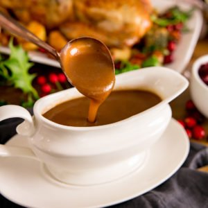 Christmas gravy being poured off a spoon into a white gravy boat
