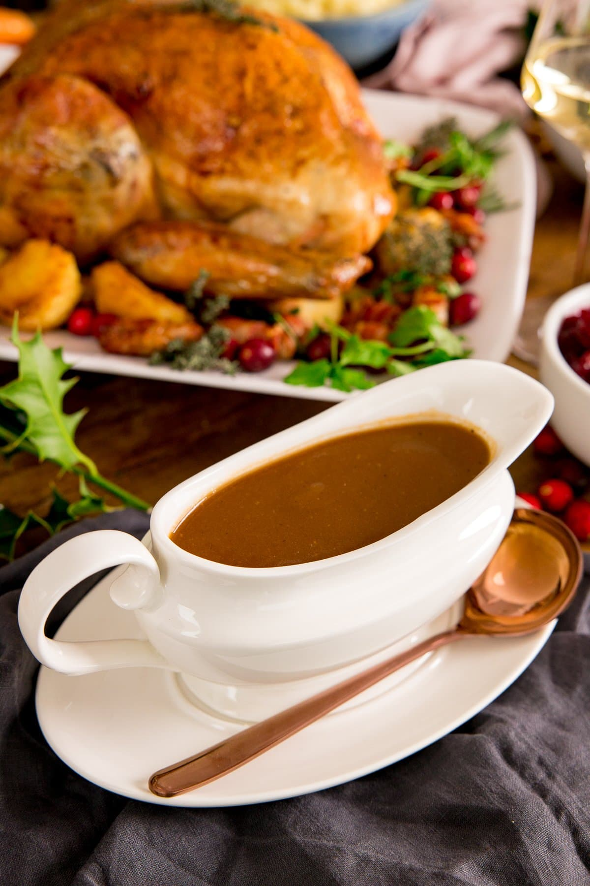 Christmas gravy in a white gravy boat with a roast turkey in the background