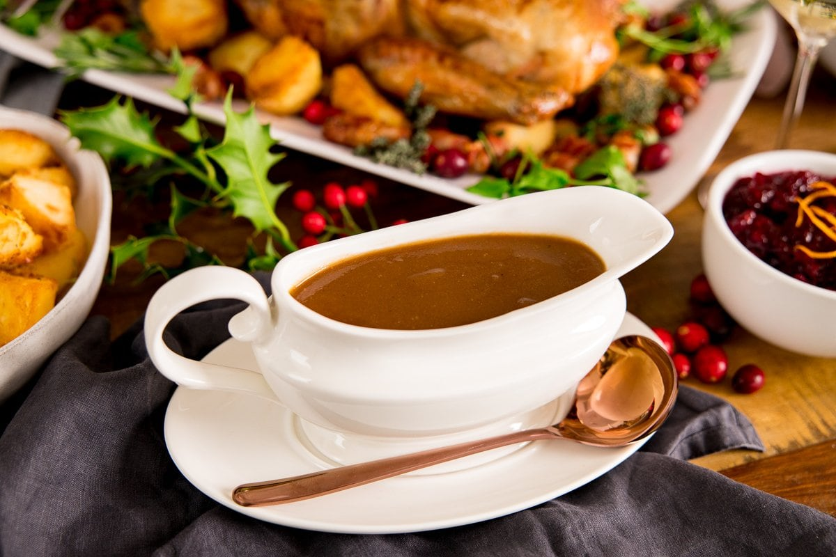 A white gravy boat filled with gravy on a table with a roast turkey and side dishes around the gravy boat. Copper spoon resting on the gravy boat saucer.