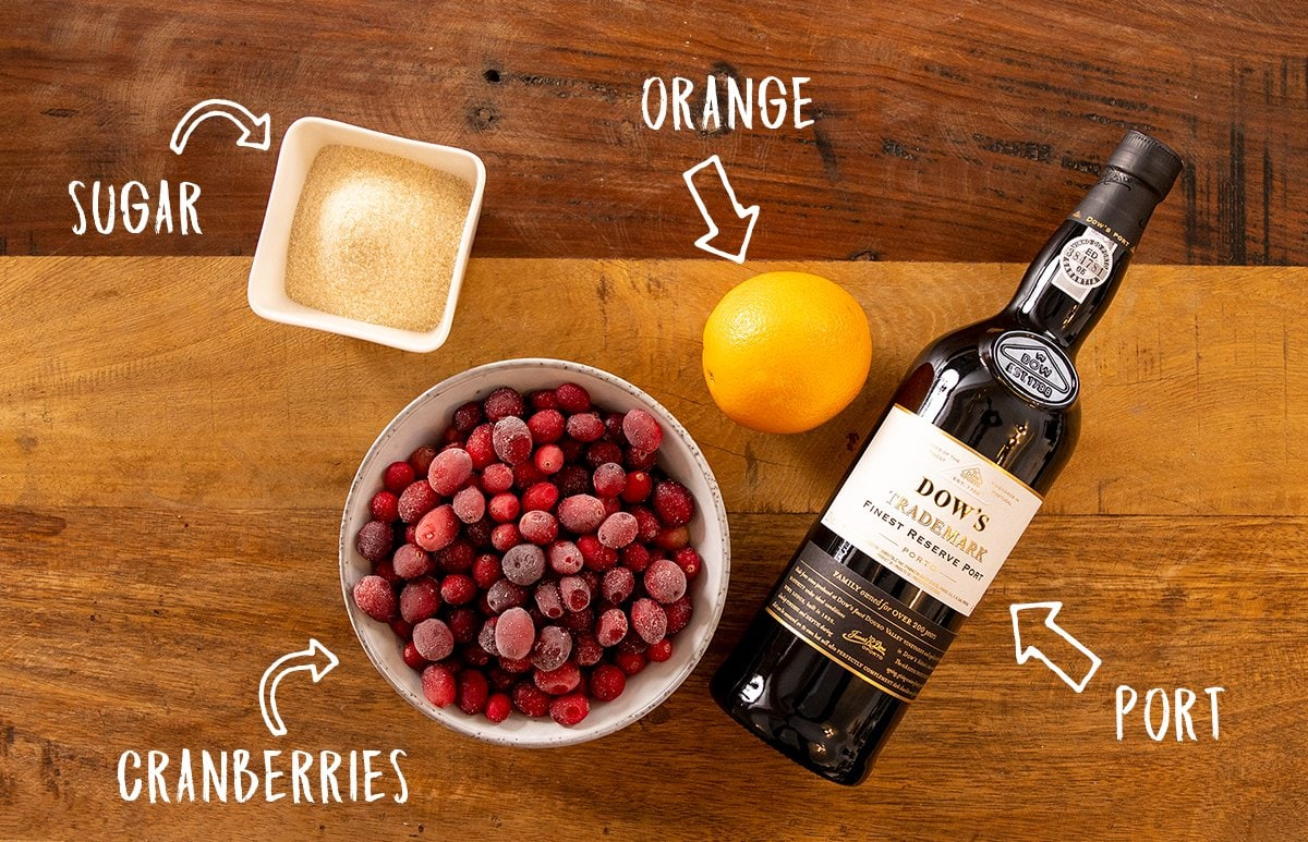 Ingredients for cranberry sauce on a wooden table.