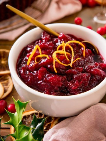 Cranberry sauce in a white bowl with orange zest on top - on a festive christmas table