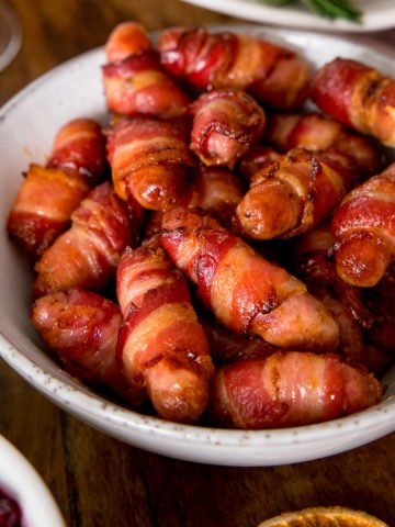 Sausages wrapped in bacon in a white bowl