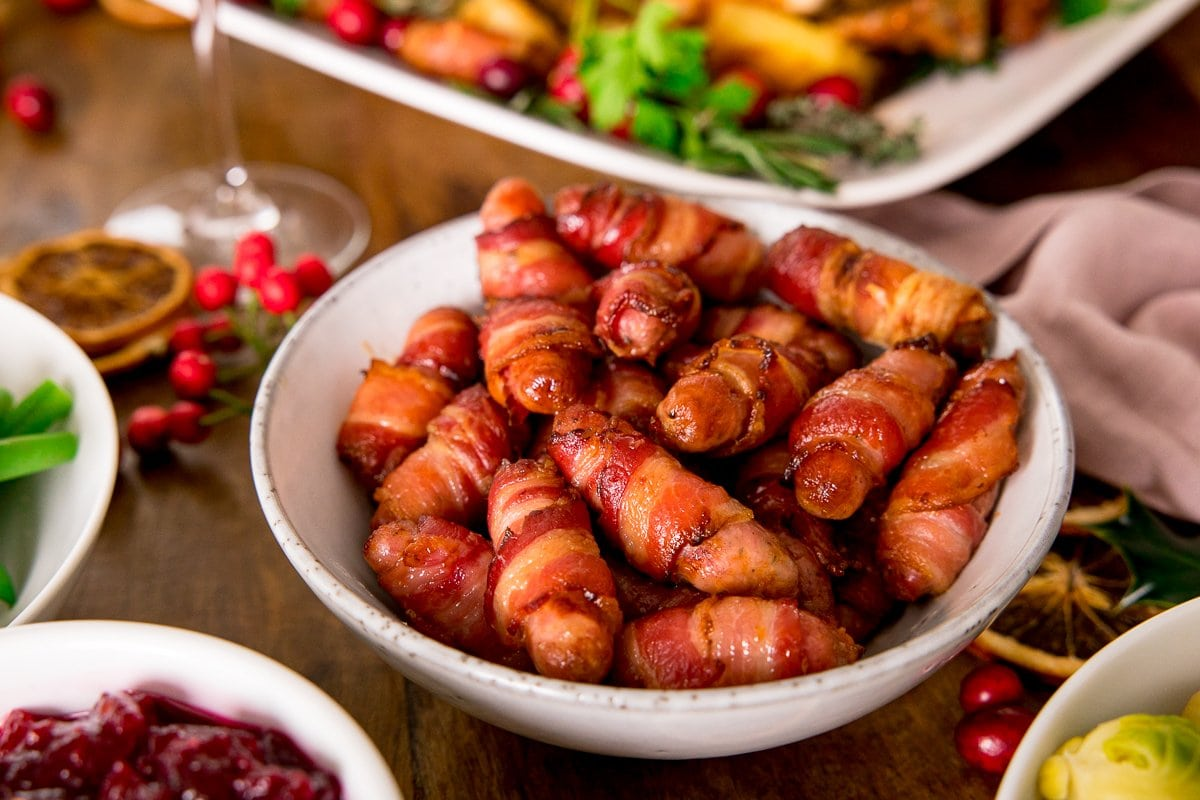 Bacon wrapped sausages in a white bowl on a table with other festive dishes partially in shot